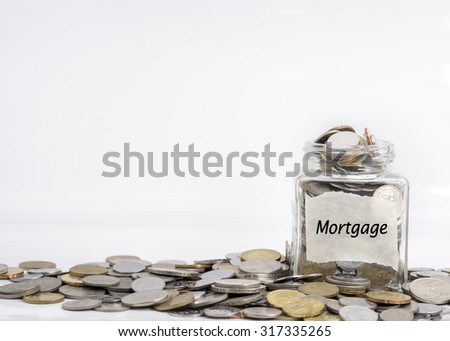 coins in jar with mortgage label in isolated white background; financial concept - stock photo
