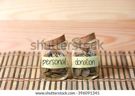 Coins in jar. Writing Personal Donation on two jar with wooden pallet background. Selective focus with shallow depth of field. - stock photo