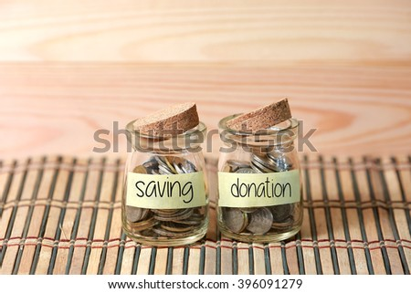 Coins in jar. Writing Saving Donation on two jar with wooden pallet background. Selective focus with shallow depth of field. - stock photo
