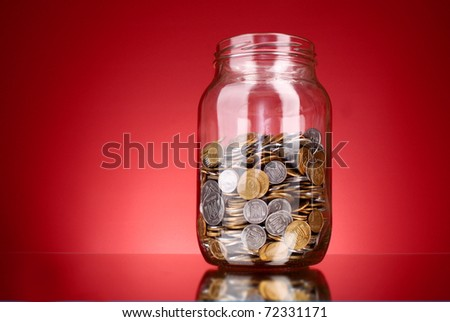 coins in money jar on red background. Ukrainian coins - stock photo