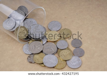 Coins in the glass isolated on wooden table. Business concept. DOF and copy space.  - stock photo