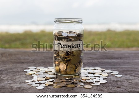 Coins in the jar or glass on the wood with PENSION label against bokeh beach background. Financial concept. selective focus - stock photo