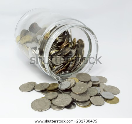 Coins inside glass jar with white background - stock photo