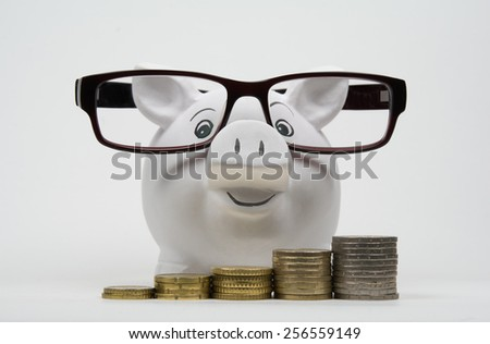 Coins lined up from short to tall stacks front of a piggy bank with glasses - stock photo