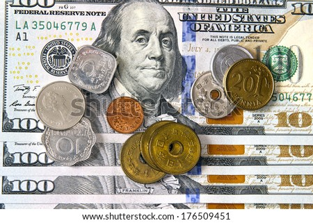 Coins of different countries on the background of the new hundred dollar American banknote - stock photo