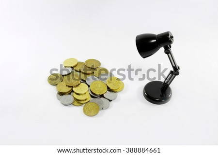 Coins of Malaysia and black mini led desk lamp isolated on white background - stock photo