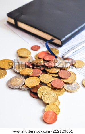 Coins on a table near agenda and a contract - stock photo