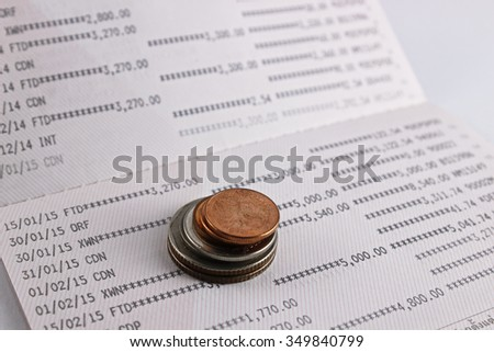 Coins on account book isolate on white background