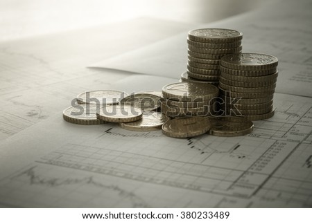 Coins placed on the report of financial graph. concept of business, finances, financial, investment. - stock photo
