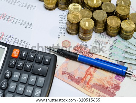 coins, ruble banknotes and calculator on table