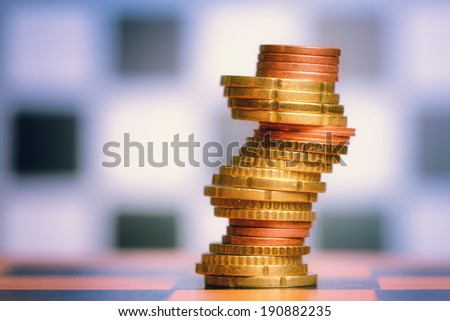 Coins shaped like knight on chess board - stock photo