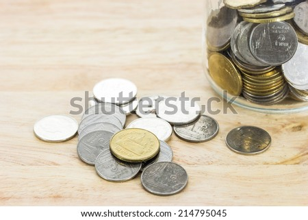 coins spilling out of a jar  - stock photo