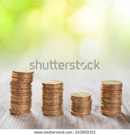 Coins stack in row on wooden background, financial concept. Focus on foreground with blur nature green background.