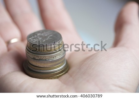 Coins stacked column in the palm of a man. - stock photo