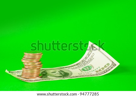 Coins stacked in bars laying on stack of 100 dollar bill over green background - stock photo