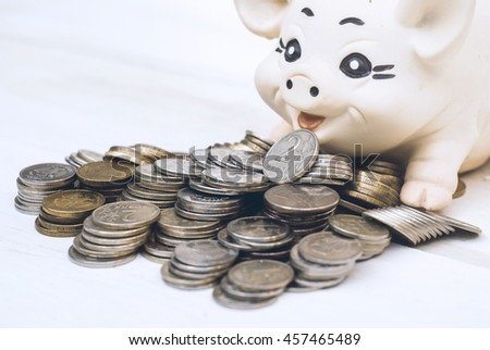 Coins with piggy bank on a wooden background.