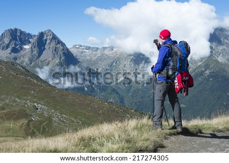 COL DE BALME, FRANCE - SEPTEMBER 01: Backpacker photographing view with Aiguille de Loriaz in the background. The area is a stage of the popular Mont Blanc tour. September 01, 2014 in Col de Balme. - stock photo