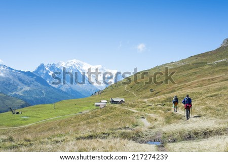 COL DE BALME, FRANCE - SEPTEMBER 01: Backpackers approraching chalet with Mont Blanc in the background. The area is a stage of the popular Mont Blanc tour. September 01, 2014 in Col de Balme. - stock photo