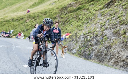 COL DU GLANDON, FRANCE - JUL 24: Portrait of a kid cyclist in plein effort,climbing the road to Col du Glandon in Alps, before the stage 19 of Le Tour de France on July 24, 2015. - stock photo