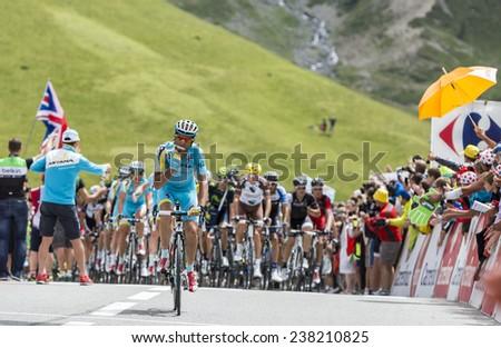 COL DU LAUTARET,FRANCE - JUL 19:The peloton arrives on Col du Lautaret in Hautes Alpes, during the stage 14 of Le Tour de France on July 19 2014. - stock photo