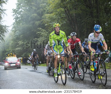 COL DU PLATZERWASEL,FRANCE - JUL 14:Cyclists riding in the peloton on the climbing road to mountain pass Platzerwasel in Vosges Mountains, during Le Tour de France on July 14 2014. - stock photo