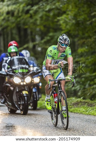 COL DU PLATZERWASEL,FRANCE - JUL 14: Peter Sagan, wearing The Green Jersey, checks the stage itinerary, while climbing the road to Col du Platzerwasel, in Vosges, during Le Tour de France on July 14 2014 - stock photo
