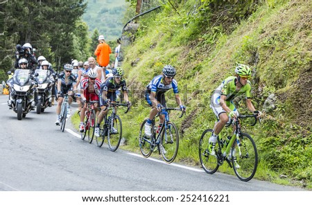 COL DU TOURMALET, FRANCE - JUL 24: Group of five cyclists following the head of the race on the difficult road to Col de Tourmalet in the stage 18 of Le Tour de France on July 24, 2014. - stock photo