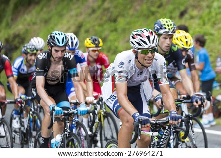 COL DU TOURMALET, FRANCE - JUL 24:The peloton climbing the difficult road to Col de Tourmalet in the stage 18 of Le Tour de France on July 24, 2014. - stock photo