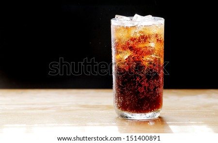 cola and ice,bubble in glass, black background. - stock photo