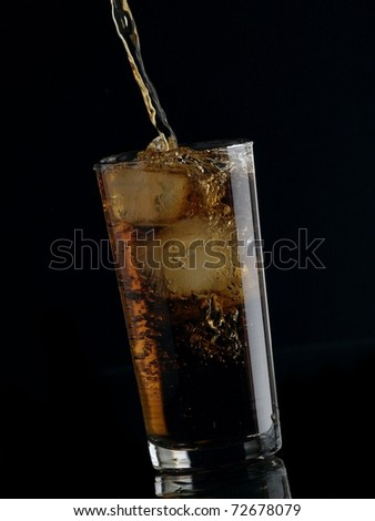 Cola flow in a glass on black background