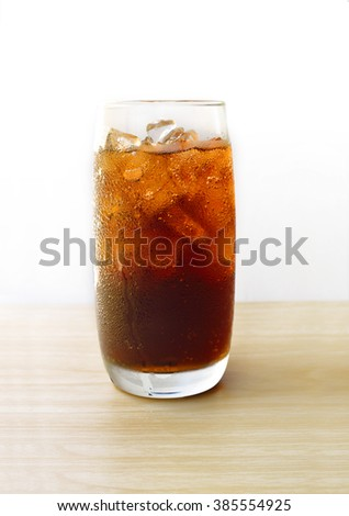 Cola in glass with ice cubes on wood table - stock photo
