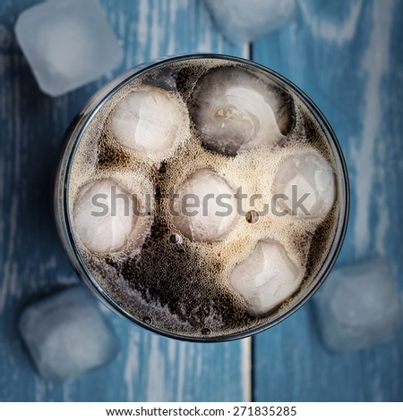 Cola in glass with ice over blue wooden table. Top view. - stock photo