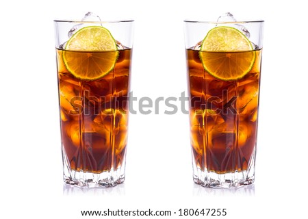 Cola in tall glasses with ice cubes and lime over white  - stock photo