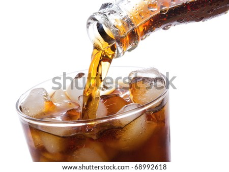 Cola is pouring into glass on white background - stock photo