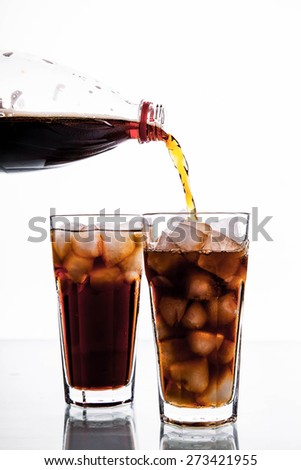 Cola is pouring into glass on white background. soft drinks - stock photo