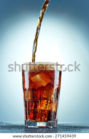 Cola pouring in a glass  with ice on a blue background - stock photo