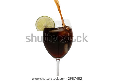 Cola pouring in a glass with lime against a white background