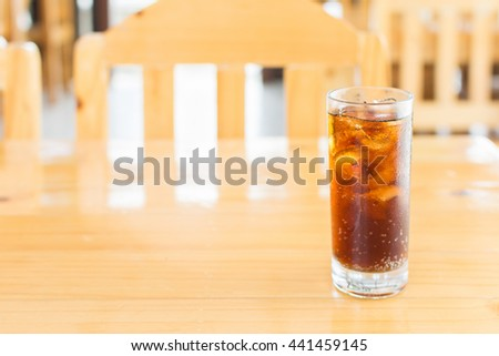 Cola soda with ice in glass on wooden table