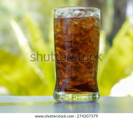 cola with ice in glass against blur nature background - stock photo