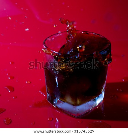 Cola with ice in glass on red background - stock photo