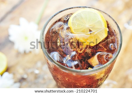 Cola with lemon slice in glass on wooden table. - stock photo
