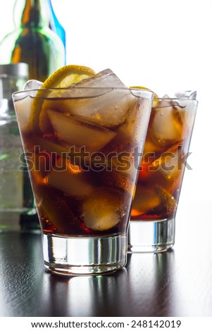 Cola with lemon slice in glass on wooden table