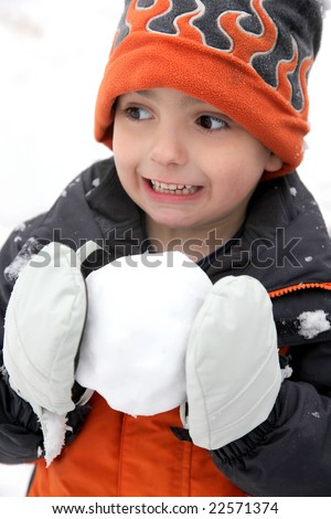 Cold adorable five year old getting ready to throw snowball. - stock photo