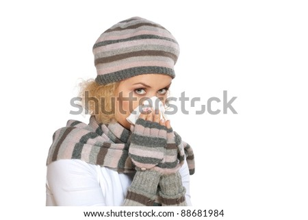 Cold, allergy, flu / Woman in a winter knit hat, scarf and gloves blowing her nose