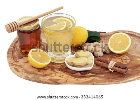Cold and flu remedy cure drink in a glass with fresh ginger, lemon, honey in a jar with dropper and cinnamon spice on an olive wood board over white background. - stock photo