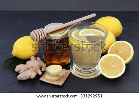 Cold and flu remedy relief drink with ginger, lemon and honey over slate background. - stock photo