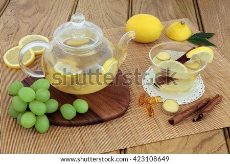 Cold and flu remedy with hot lemon, honey and ginger drink in glass tea cup and teapot, with grapes, spices and  multi vitamin tablets on maple board over bamboo and oak background. - stock photo