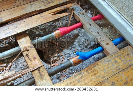 Cold and hot water pipes under a broken wood floor - stock photo
