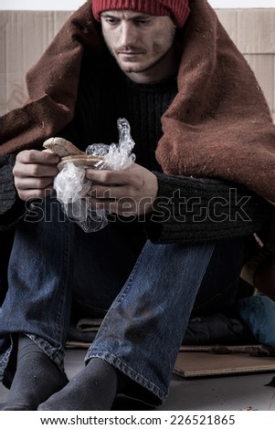 Cold and sad homeless man is eating a bread on the street