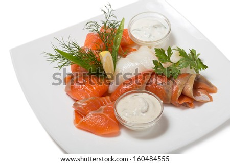 Cold appetizer of smoked halibut, salted trout, sockeye salmon salting cognac with lemon cream mushroom sauce. - stock photo